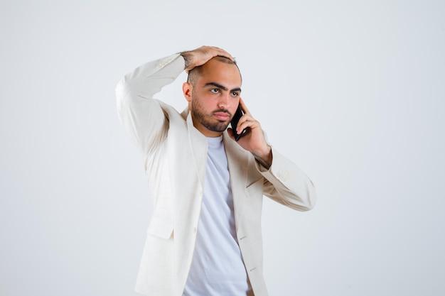 Jovem em t-shirt branca, jaqueta, falando ao telefone e colocando a mão na cabeça e olhando com raiva, vista frontal.