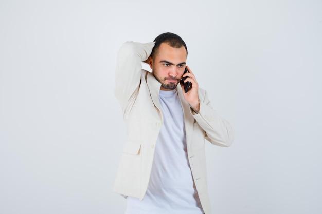 Jovem em t-shirt branca, jaqueta falando ao telefone e colocando a mão na cabeça e olhando sério, vista frontal.