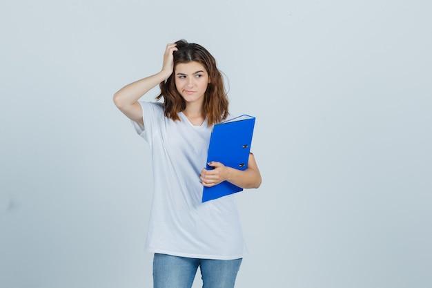 Jovem em t-shirt branca segurando uma pasta, mantendo a mão na cabeça e parecendo frustrada, vista frontal.