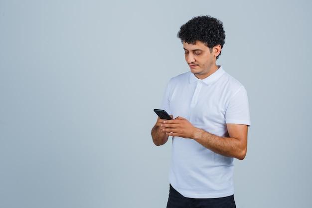 Jovem em t-shirt branca usando telefone celular e olhando ocupado, vista frontal.