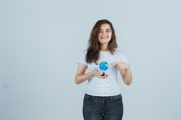 Jovem em t-shirt, jeans, apontando o globo e parecendo feliz, vista frontal.