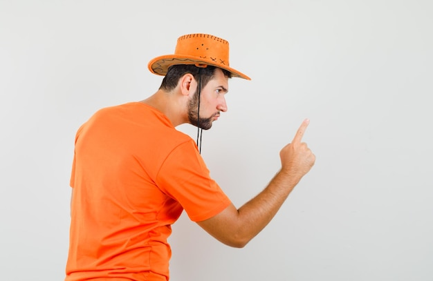 Jovem em t-shirt laranja, chapéu avisando alguém com o dedo e parecendo furioso.