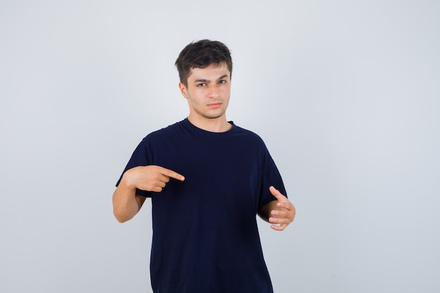 Jovem em t-shirt preta apontando para a palma da mão espalhada e olhando sério, vista frontal.