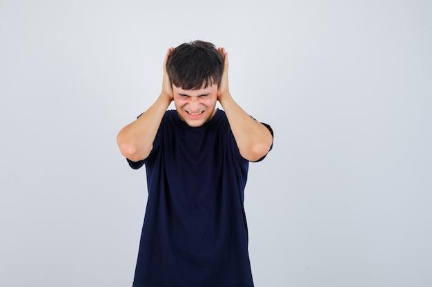 Jovem em t-shirt preta de mãos dadas nas orelhas e parecendo irritado, vista frontal.
