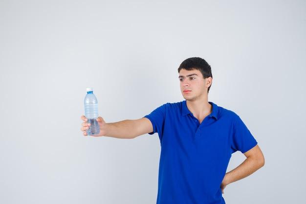 Jovem em t-shirt, segurando a garrafa de plástico na mão e olhando confiante, vista frontal.