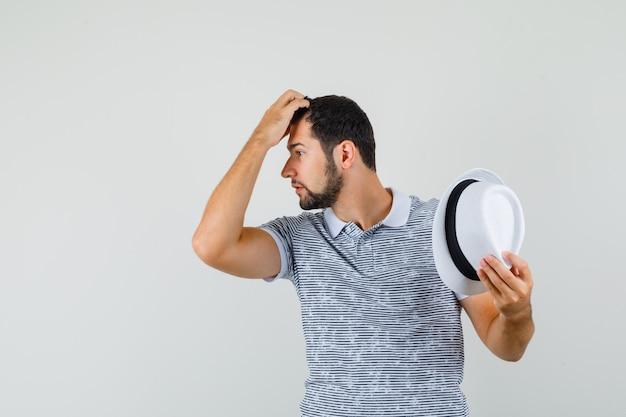 Jovem em t-shirt tirando o chapéu e coçando a cabeça e olhando pensativo, vista frontal.