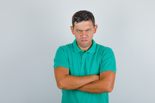 Jovem em t-shirt verde em pé com os braços cruzados e olhando com raiva, vista frontal.