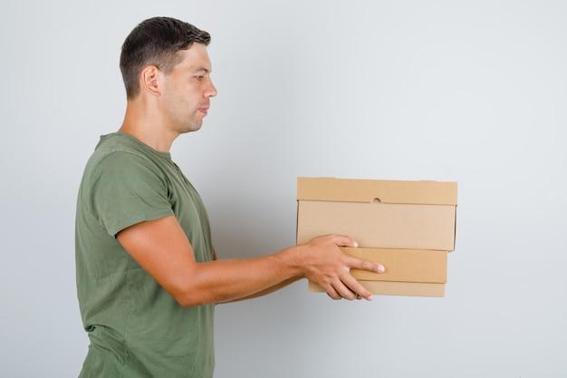 Jovem em t-shirt verde exército segurando caixas de papelão.