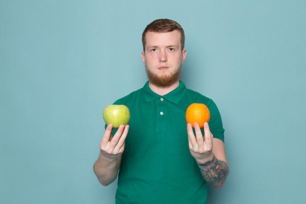 Jovem em t-shirt verde segurando frutas
