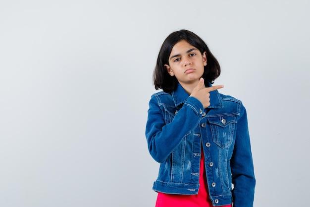 Jovem em t-shirt vermelha e jaqueta jeans apontando para a direita com o dedo indicador e olhando séria, vista frontal.