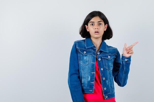 Jovem em t-shirt vermelha e jaqueta jeans apontando para a direita com o dedo indicador e olhando surpresa, vista frontal.