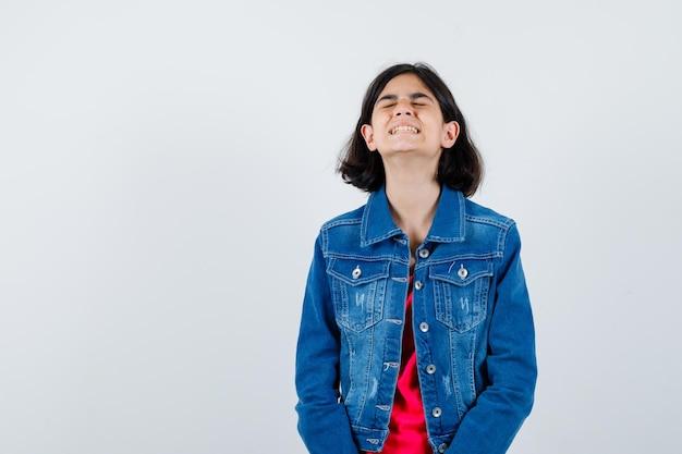 Jovem em t-shirt vermelha e jaqueta jeans em pé em linha reta, fechando os olhos e posando para a câmera e parecendo aflita, vista frontal.