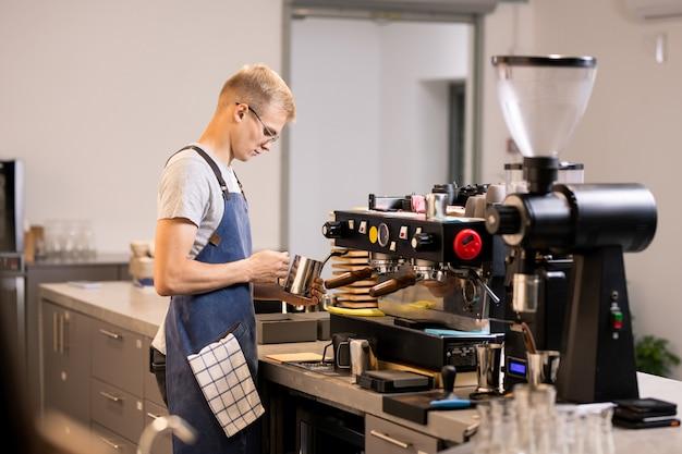 Jovem em traje de trabalho segurando uma caneca de aço perto da máquina de café enquanto prepara bebidas para os clientes de sua própria cafeteria ou bistrô