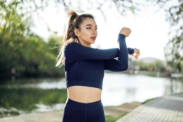 Jovem em traje esporte azul escuro, se exercitando no parque