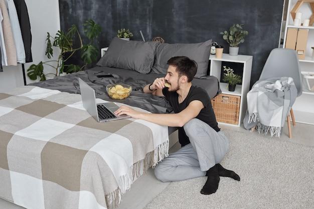 Jovem em trajes caseiros sentado no chão do quarto e usando o laptop enquanto come batatinhas durante o auto-isolamento