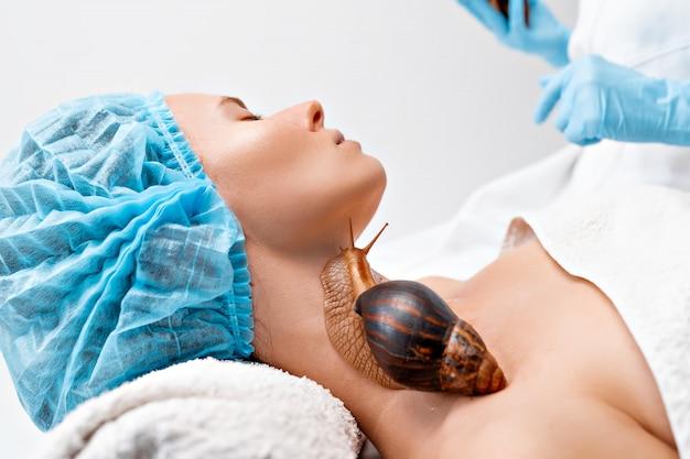 Jovem em tratamento com caracóis gigantes de achatina no salão de beleza