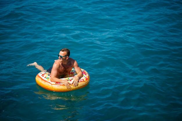 Jovem em um anel inflável no mar, descansando e nadando em um dia ensolarado