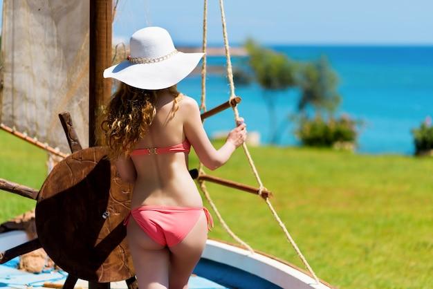 Jovem em um barco segurando a roda. retrato de uma menina com chapéu branco olhando o mar