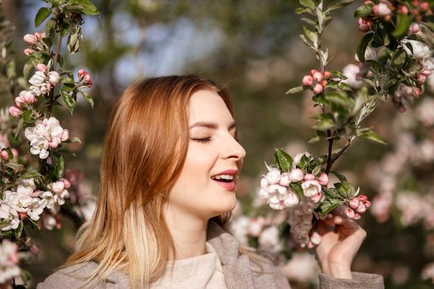 Jovem em um pomar de maçã florescendo