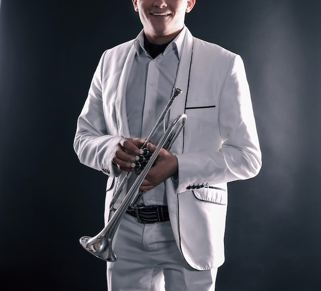 Jovem em um terno branco com um trumpet.isolated em fundo preto.