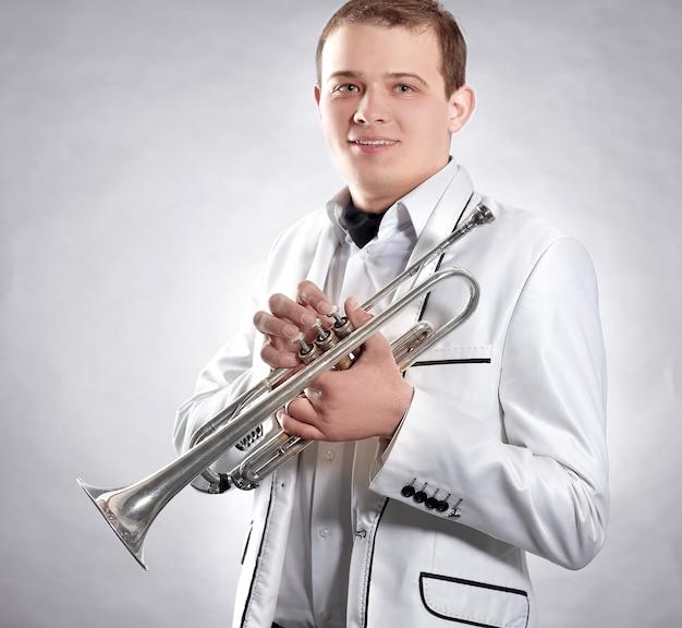 Jovem em um terno branco com uma trombeta.