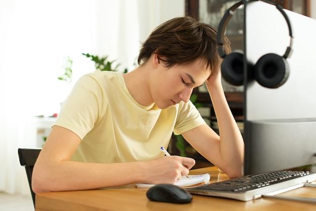 Jovem em uma camiseta amarela funciona em casa no computador. bate-papo on-line. trabalho remoto via internet em isolamento