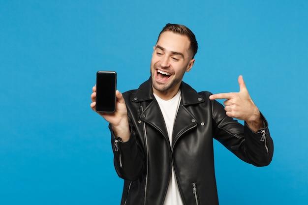 Jovem em uma jaqueta preta e camiseta branca segurar o telefone móvel com a tela em branco vazia para conteúdo promocional isolado no retrato de estúdio de fundo de parede azul. conceito de estilo de vida de pessoas. simule o espaço da cópia