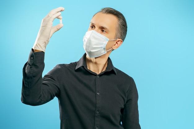 Jovem em uma máscara médica protetora e luvas com uma cápsula ou comprimido nas mãos, sobre um fundo azul. conceito de cuidados de saúde e medicina.