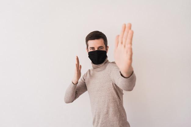 Jovem em uma máscara protetora preta. equipamento de proteção individual para coronovírus. máscara caseira para acesso a locais públicos