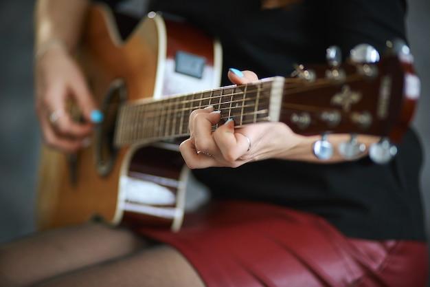 Jovem em uma minissaia de couro vermelho e meia-calça preta tocando violão