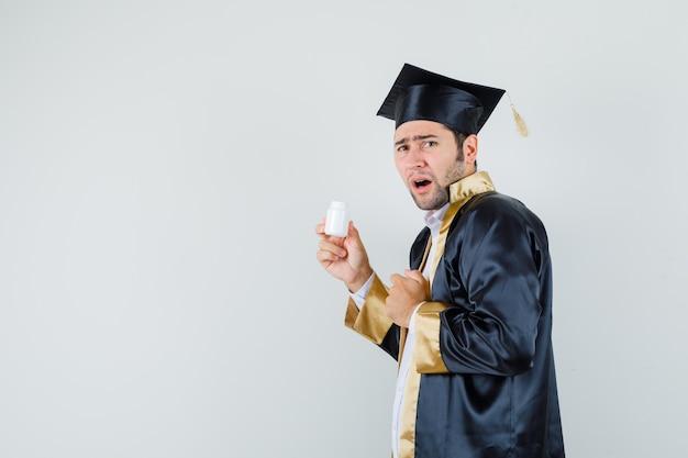 Jovem em uniforme de pós-graduação segurando o frasco aberto de comprimidos e parecendo enojado.