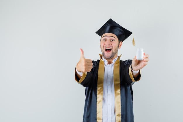 Jovem em uniforme de pós-graduação segurando o frasco de comprimidos, aparecendo o polegar e parecendo feliz, vista frontal.