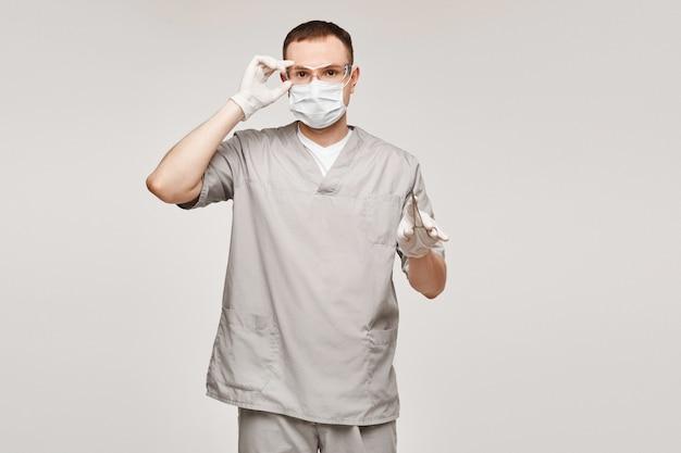 Jovem em uniforme médico e óculos de proteção
