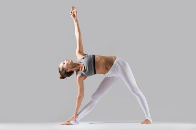 Jovem em utthita trikonasana pose, fundo de estúdio cinza