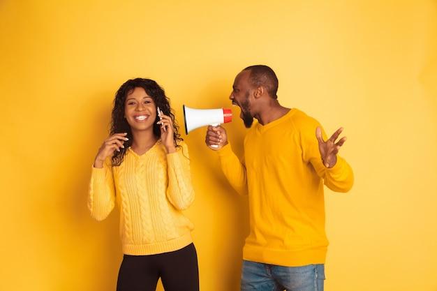 Jovem emocional afro-americano e mulher com roupas casuais brilhantes no espaço amarelo