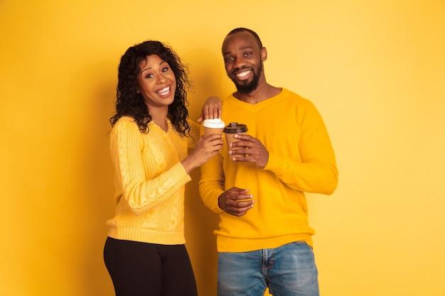 Jovem emocional afro-americano e mulher em roupas casuais brilhantes sobre fundo amarelo. casal bonito. conceito de emoções humanas, expressão facial, relações, anúncio. beber café juntos.