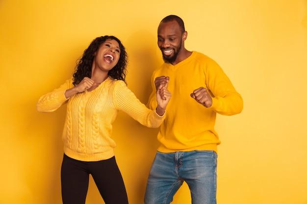 Jovem emocional afro-americano e mulher em roupas casuais brilhantes sobre fundo amarelo. casal bonito. conceito de emoções humanas, expressão facial, relações, anúncio. dançando e cantando.