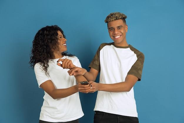 Jovem emocional afro-americano e mulher posando sobre fundo azul. casal bonito. conceito de emoções humanas, expressão facial, relações, anúncio. assistir tv junto, seu canal favorito.