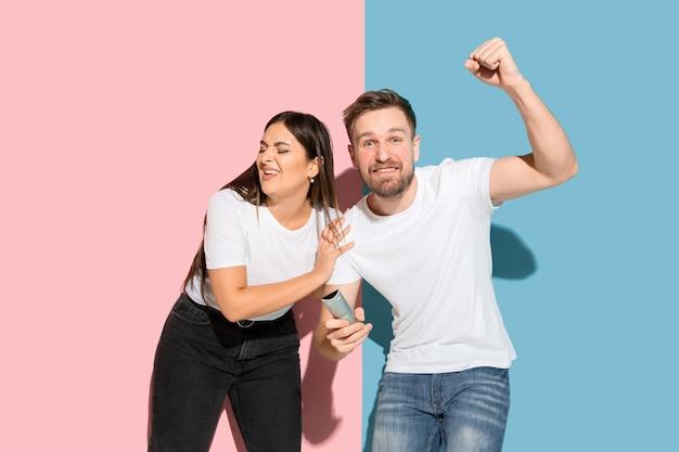 Jovem emocional e mulher na parede rosa e azul