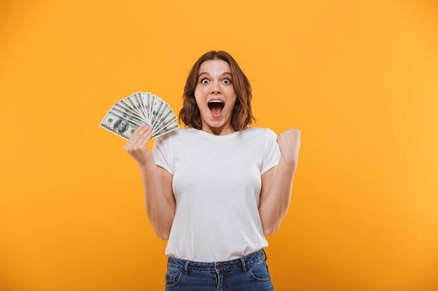 Jovem emocional segurando dinheiro faz gesto de vencedor.