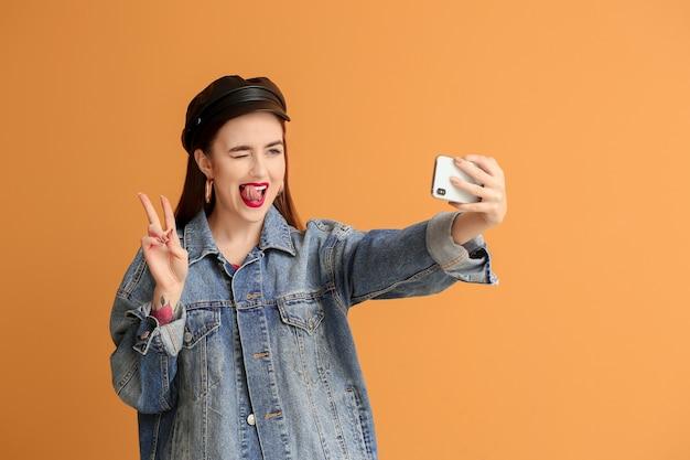 Jovem emocional tirando uma selfie em laranja