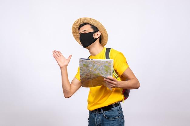 Jovem empolgado de frente com máscara e mochila vermelha segurando mapa fechando os olhos