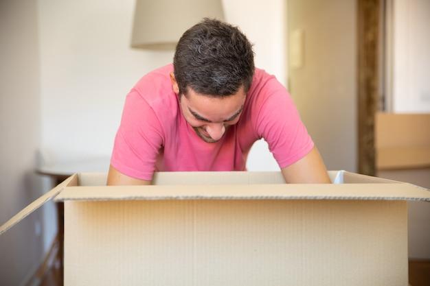 Jovem empolgado desempacotando coisas em seu novo apartamento, abrindo a caixa de papelão,