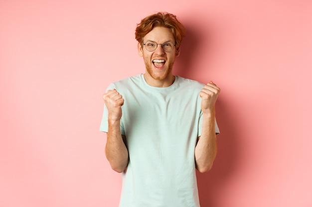 Jovem empolgado ganhando o prêmio, gritando de alegria e triunfo, fazendo o punho cerrar e dizendo que sim, de pé sobre um fundo rosa.