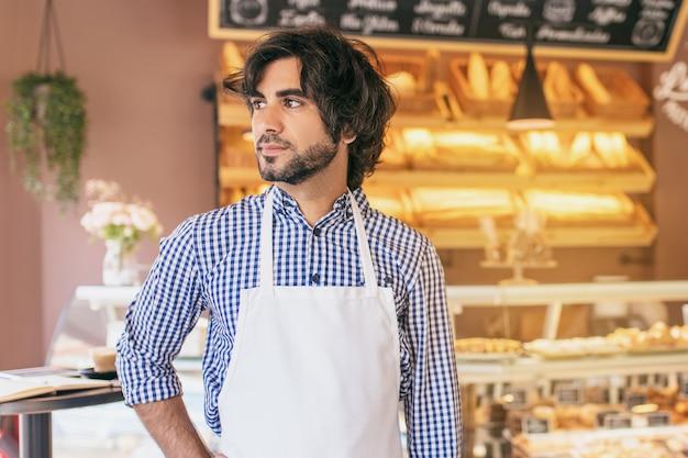 Jovem empreendedor, acaba de abrir sua padaria e se sente muito bem.