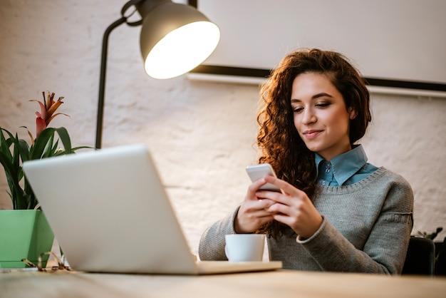 Jovem empreendedor no seu local de trabalho usando o laptop e telefone.
