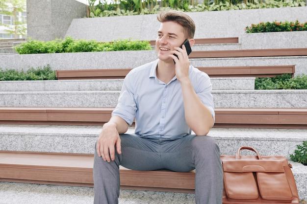 Jovem empreendedor positivo sentado em um banco de madeira ao ar livre e falando ao telefone com um colega