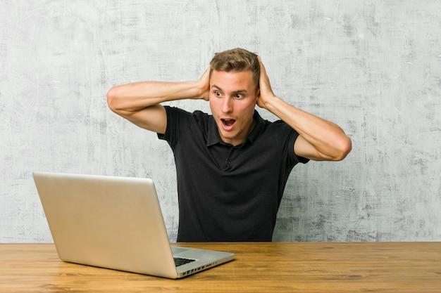 Jovem empreendedor trabalhando com seu laptop em uma mesa cobrindo os ouvidos com as mãos tentando não ouvir som muito alto