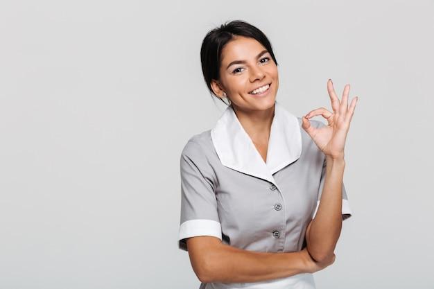 Jovem empregada atraente de uniforme mostrando o gesto ok em pé