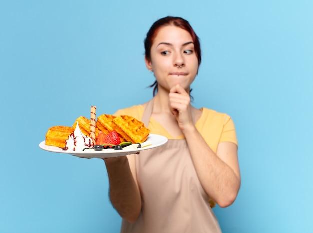 Jovem empregada de padaria com waffles e bolos